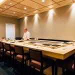 sushi man dietro al balcone di legno